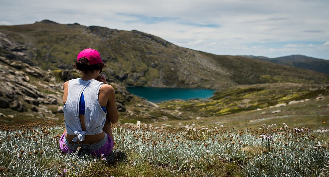 Woman sitting among wild flowers in the Snowy Mountains