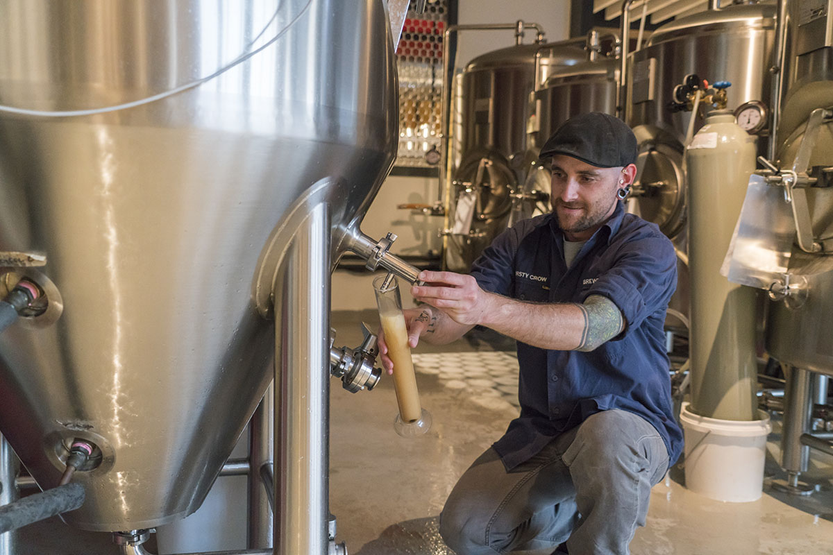 Man using the tap to draw beer from a steel industrial brewing machine, food manufacturing, microbrewery, food processing, Wagga Wagga, regional NSW